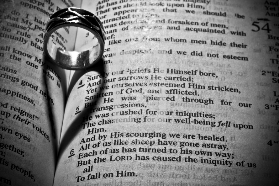 wedding band forming a heart shadow over the pages of a Bible