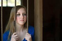 teen girl hiding behind bars with tears in her eyes