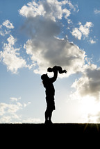 silhouette of a mother holding her child in the air