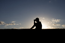 silhouette of a boy child sitting in the grass praying