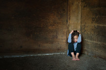 young girl hiding in a corner