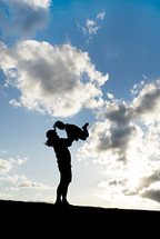 silhouette of a mother holding up her child outdoors