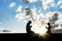 silhouette of a mother and child kneeling in prayer between a sunburst