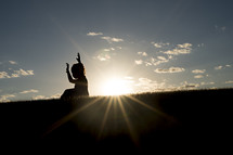 silhouette of a young girl with raised hands and a sunburst