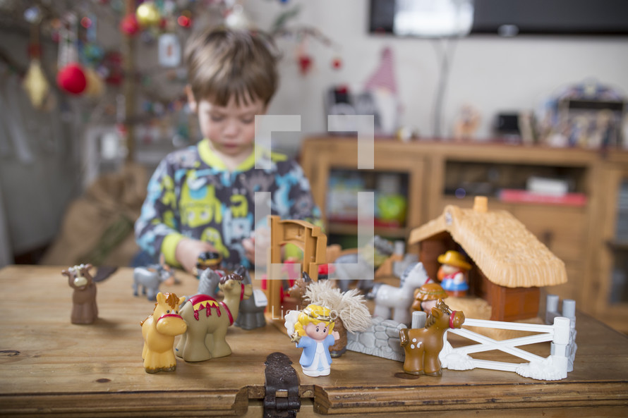 a child playing with a nativity scene toy