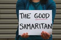 A woman holding a sign that reads the Good Samaritan