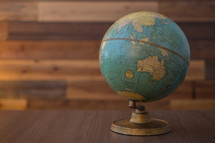 Vintage globe sites on table with wood backdrop.