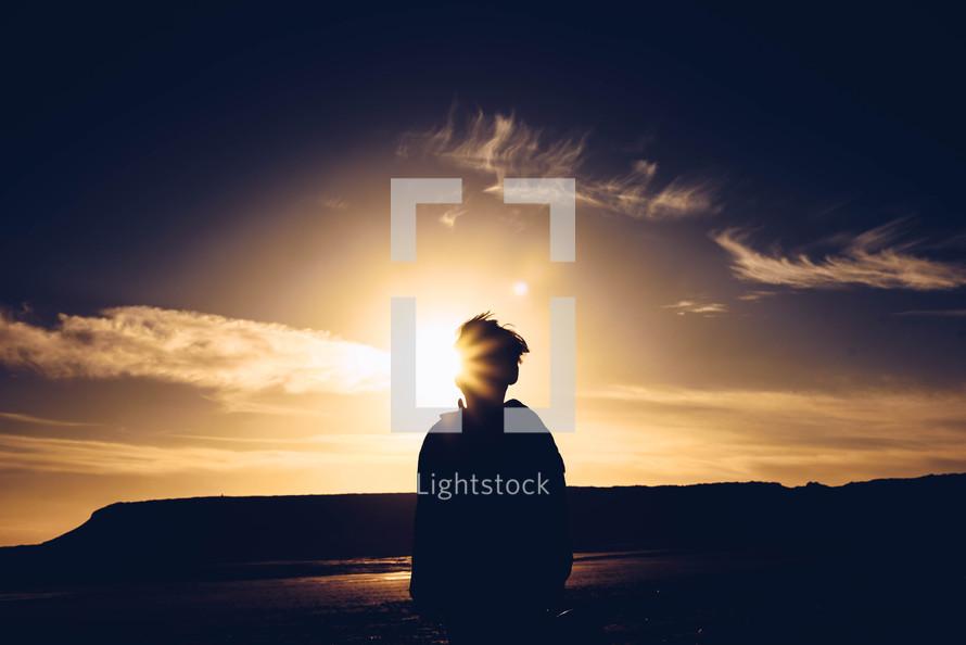 a boy standing on a beach with a sunburst
