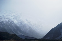clouds over snowy mountain peaks in New Zealand