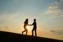 silhouettes of a young happy couple dancing at sunset