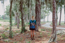 young woman with a backpack standing off a trail
