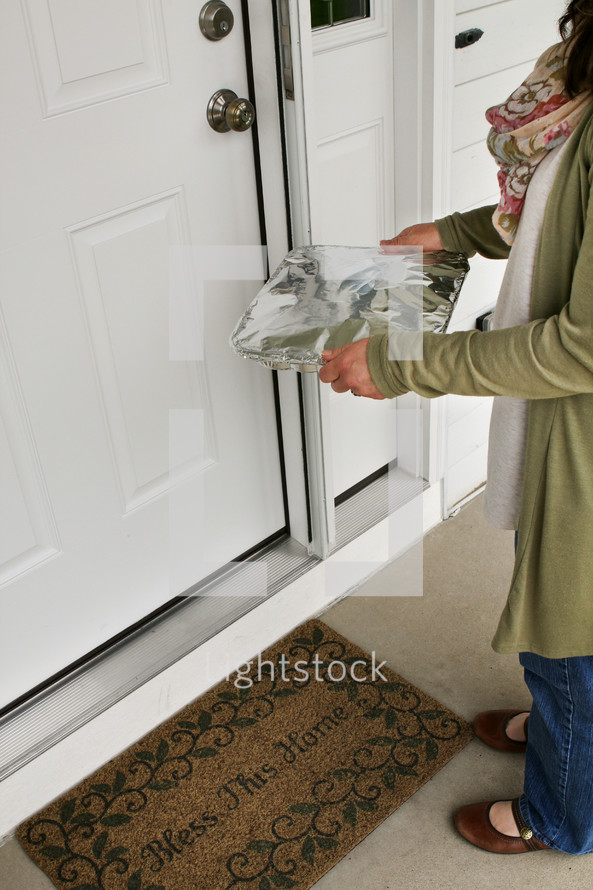 a woman bringing a pan of food to a neighbor