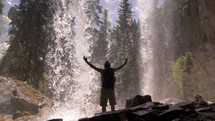 Man standing under a waterfall with arms raised to the sky.