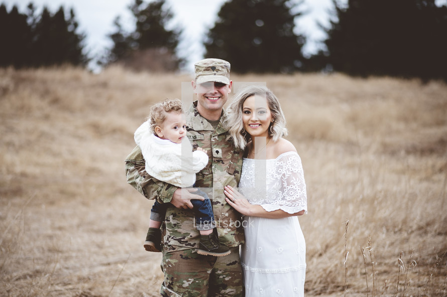 soldier in a field with his family