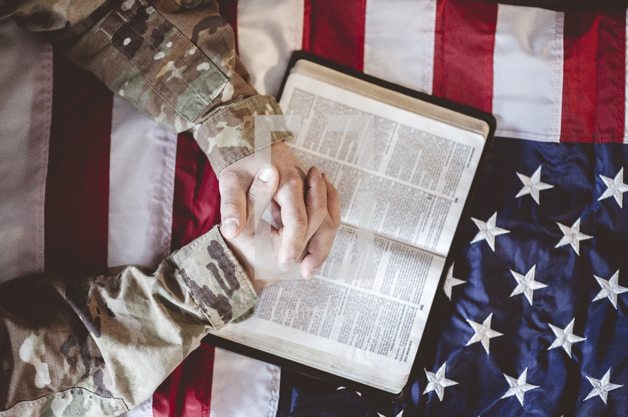serviceman with praying hands over a Bible