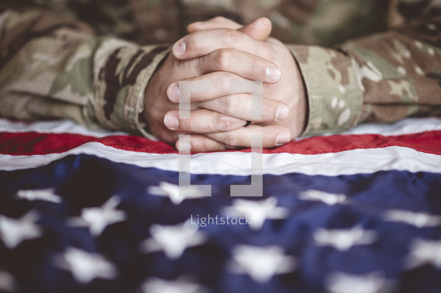 praying hands over an American flag