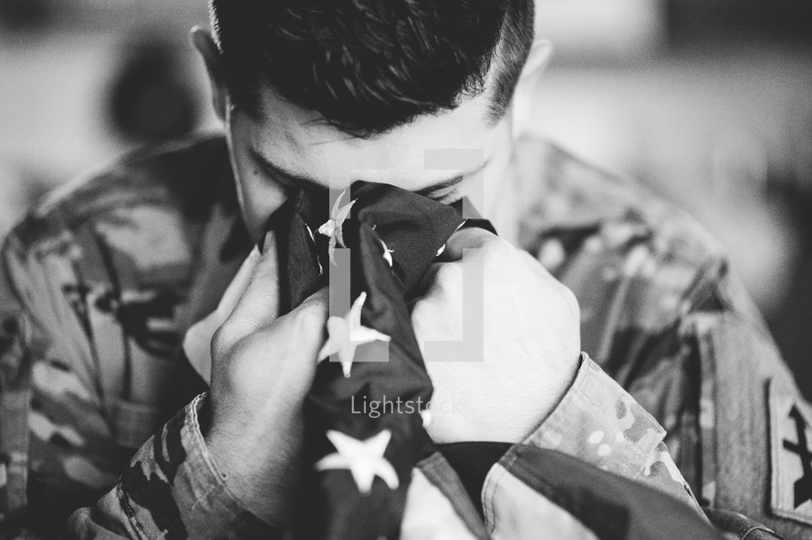 soldier crying into an American flag