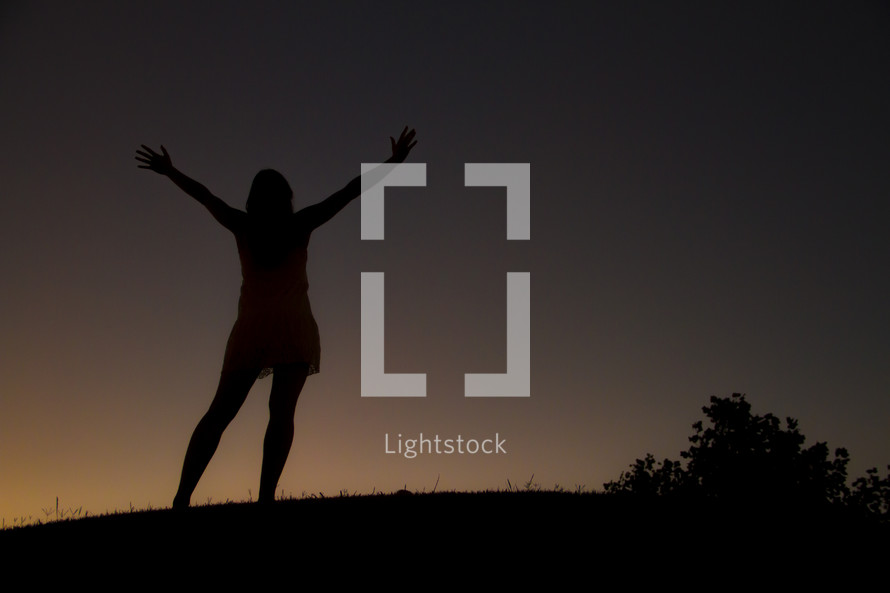 silhouette of a woman with raised arms at night