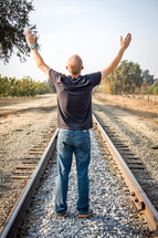 man with arms raised in worship on railroad tracks