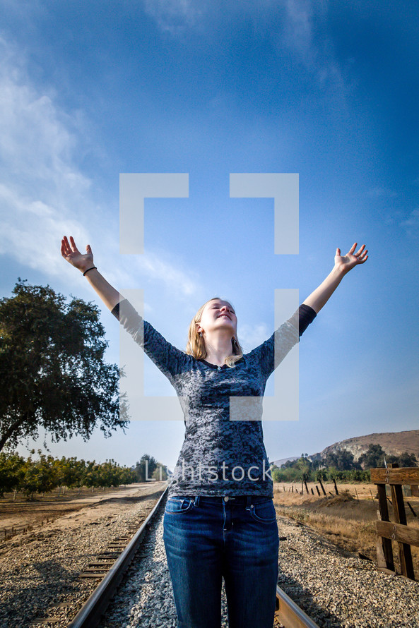 woman with hands raised in worship to God standing on train tracks