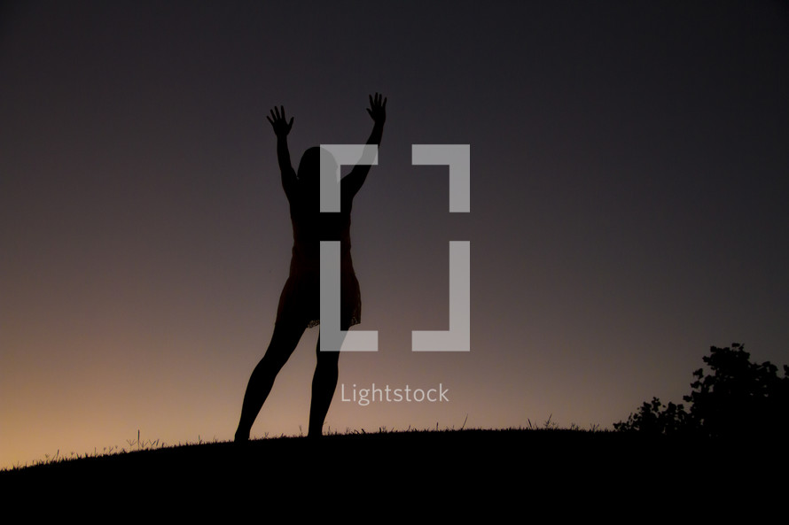 silhouette of a woman with raised hands at night