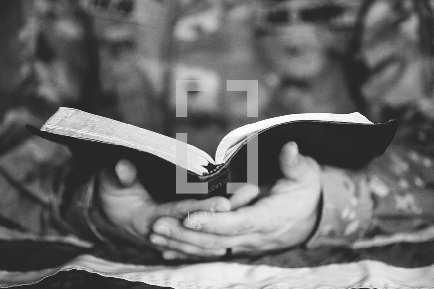 man in military uniform reading a Bible
