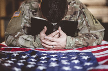 soldier praying with a Bible