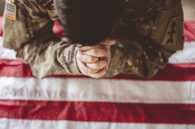 serviceman with head bowed praying over and American flag