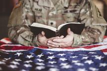 serviceman reading a Bible over an American flag