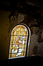 old and crumbling stained glass window in an abandoned church
