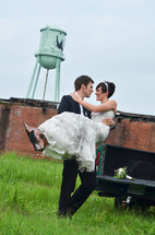 rural setting with a groom carrying his bride