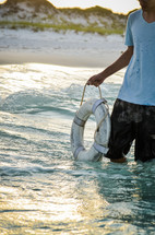 man holding a life ring while standing in the ocean