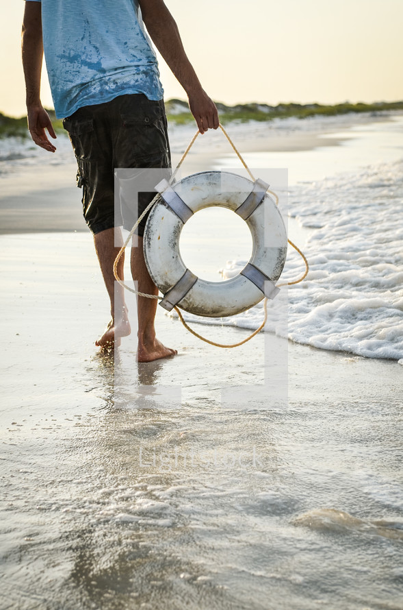 man carrying a life ring on a beach