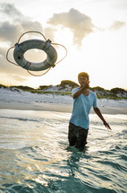 man tossing a life preserver into the ocean