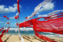 red and white banners waving on a beach
