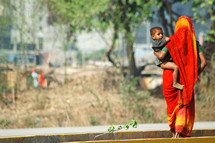mother carrying her toddler in india