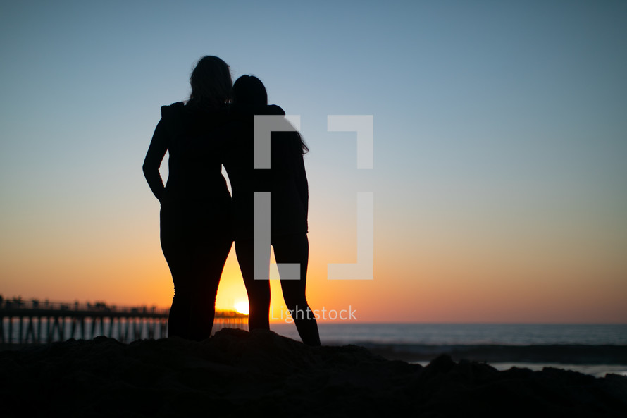 silhouettes of fiends hugging on a beach