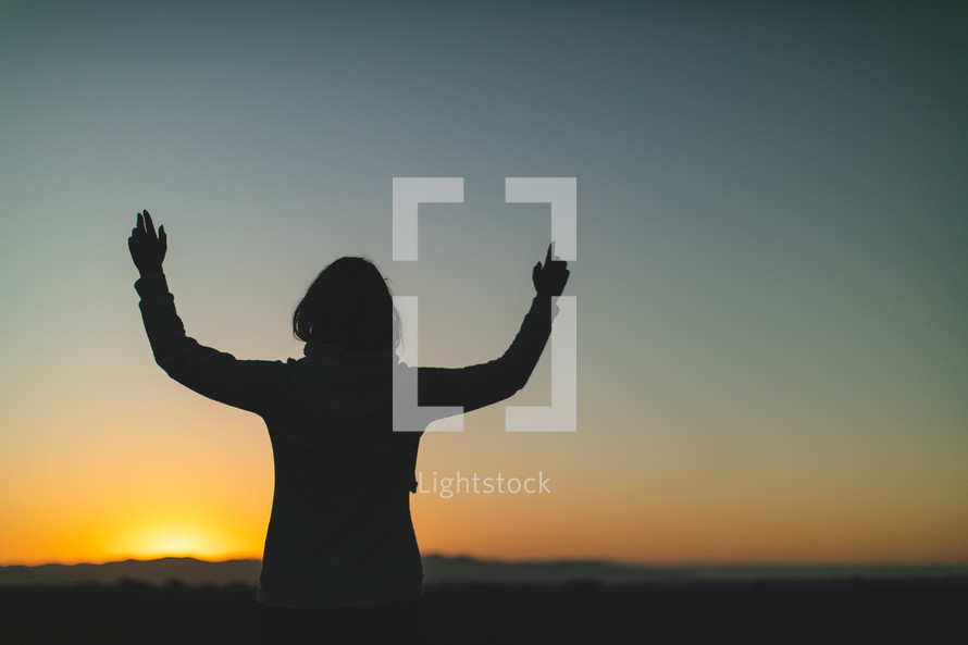 a woman looking out into a field at sunset with raised hands