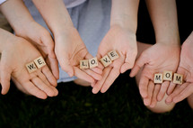 children holding scrabble pieces that read we love mom