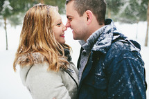 a couple standing in the snow