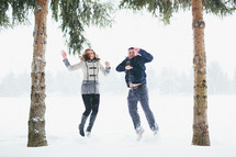 a couple jumping in the snow