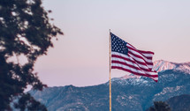 American flag on a flag pole with mountains in the background