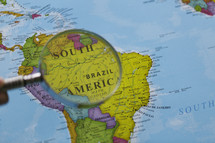 magnifying glass over a map of South America
