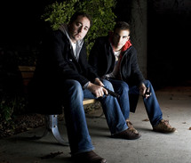 Fellowship Is Made & Broken By Choice; two men sitting on a bench at night, one holding a cross and one holding a pistol.