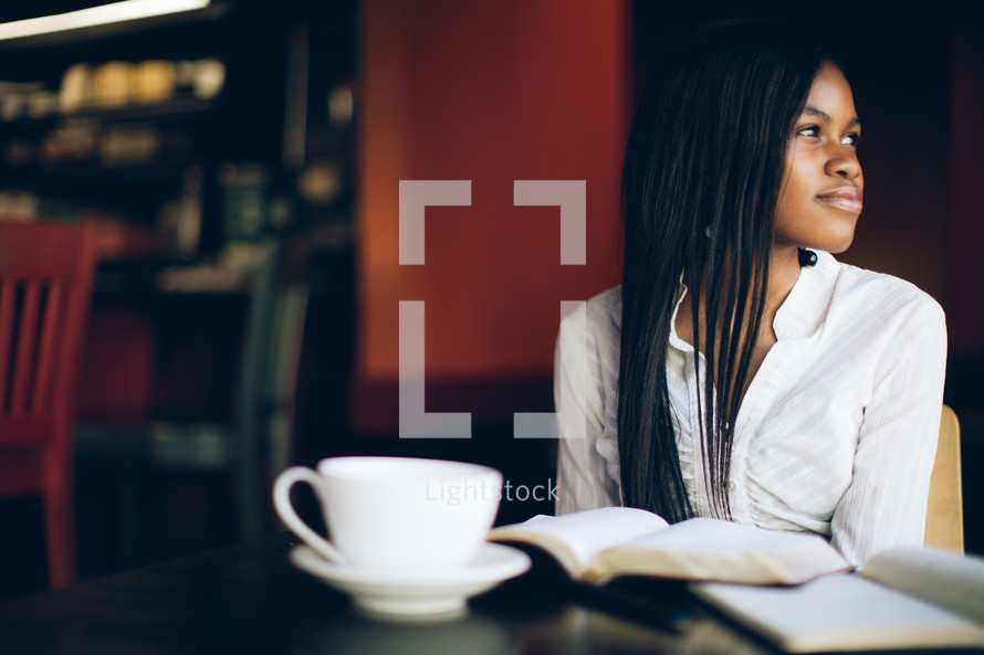 woman with her head turned to the side sitting in front of a Bible and a coffee mug at a coffee house