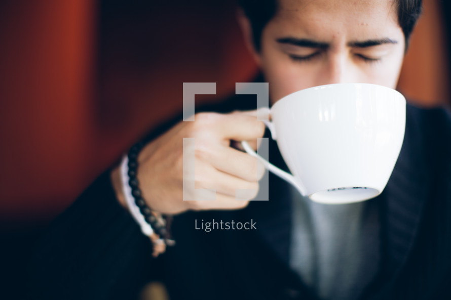 Man drinking out of white coffee cup wioth eyes closed.