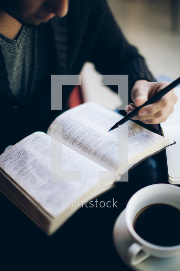man reading a Bible and underling significant verses