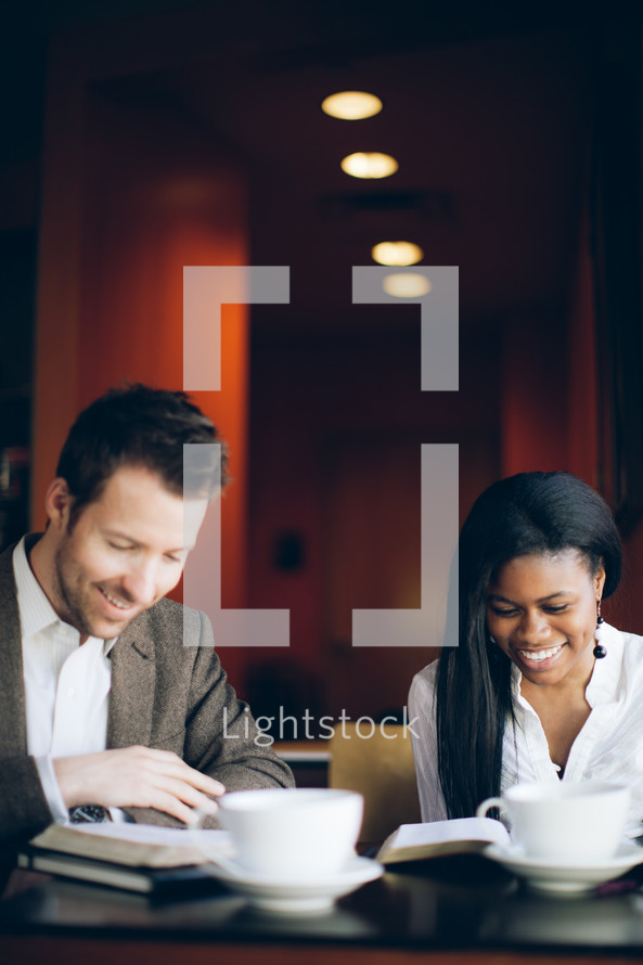 man and woman reading from a Bible at a coffee house during a Bible study