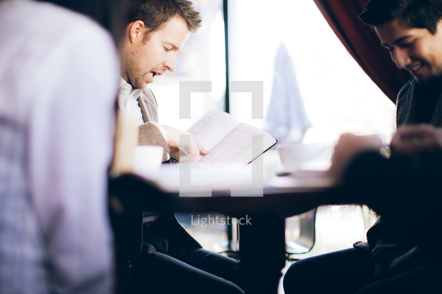 man reading from a Bible at a Bible study