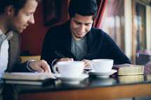 two men reading a Bible and talking over coffee during a Bible study